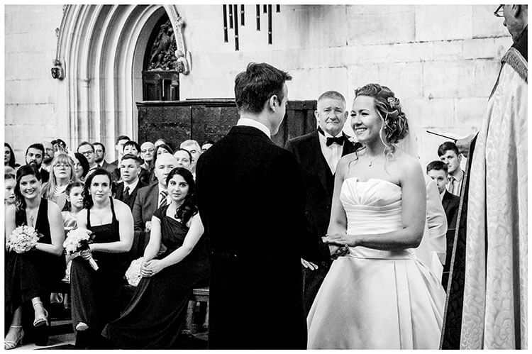Smiling bride looks at groom as she holds his hand during Kings College Chapel wedding