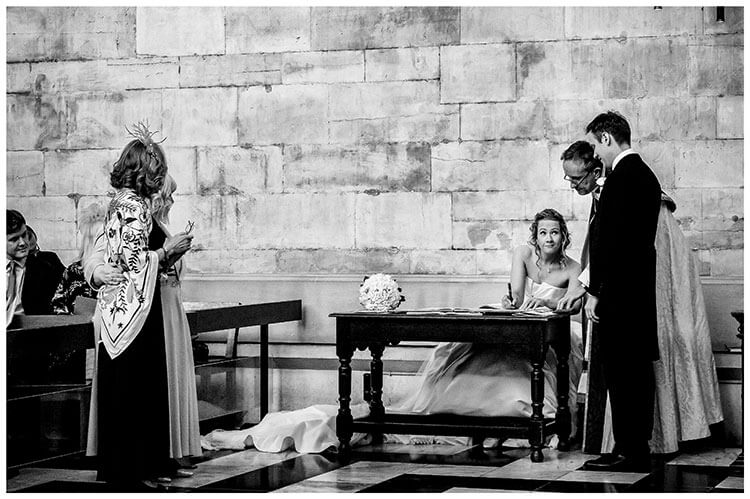 Bride looks up at groom as she signs register watched by vicar and mothers favourite wedding photography 2018