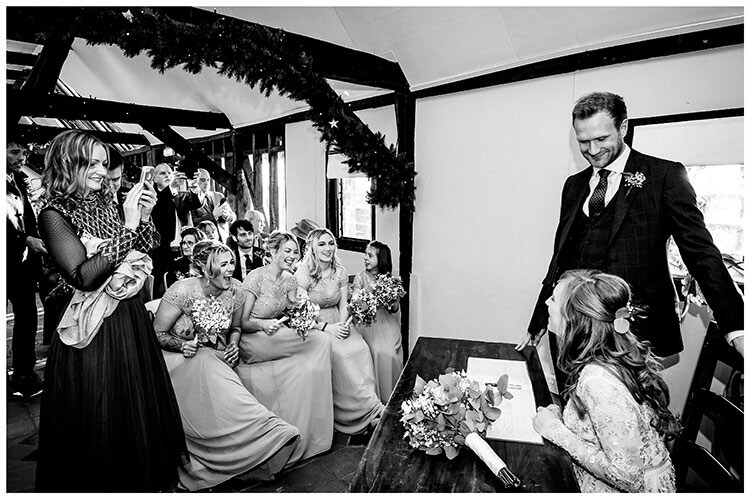 Sitting bride laughing with bridesmaids during sign of the register standing groom looks lovingly at bride whilst femaale guest takes photo on her phone of the bride and groom durign South Farm wedding venue wedding
