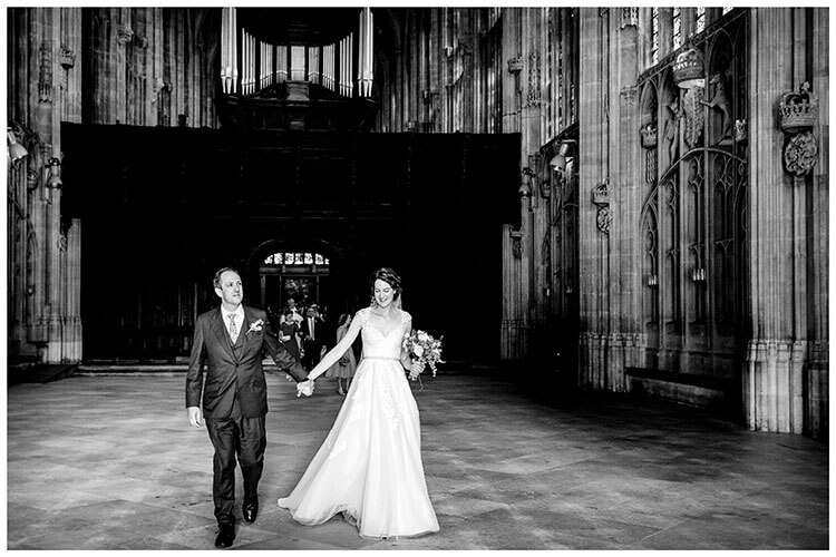 Smiling Bride groom walk hand in hand out of Kings College chapel after their wedding ceremony followed by all their guests