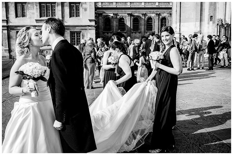 Bride and groom kiss out side kings college chapel watched by bridesmaids all the guests in background