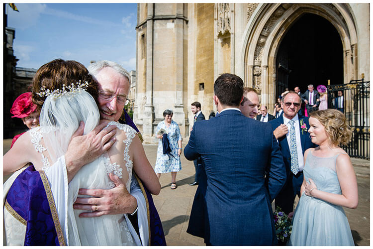 Bride hugged by vicar as groom congratulated by bestman and bridesmaid favourite wedding photography 2018