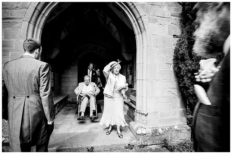 As ushers go into church old lady leaves church holding her hat followed by old gent in wheel chair favourite wedding photography 2018
