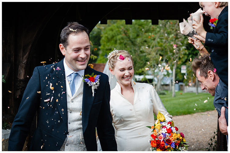Smiling bride groom have confetti thrown at them by young boy on the shoulders of bestman favourite wedding photography 2018