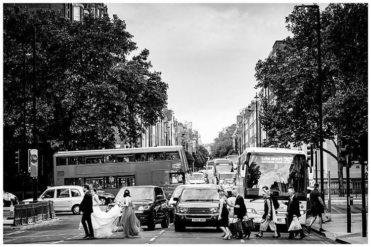 Bridal party cross road as cars wait and bus passes in background during London wedding favourite wedding photography 2018