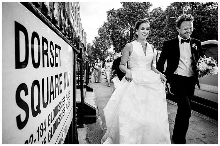 Smile bride and groom walking along street pass sign for Dorset Square in London followed by guests, bride lifts front of dress groom carrying bride bouquet during London favourite wedding photography 2018