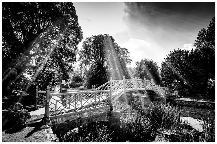 Bride and groom standing on bridge, in the grounds of Island Hall wedding venue in Cambridgeshire, drink Champagne as wonderful rays of light shine down on them favourite wedding photography 2018