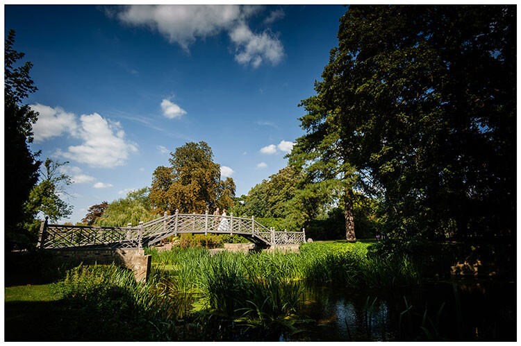 Bride and groom enjoy a moment together on ornate wooden bridge in the grounds of Cambridgeshire wedding venue Island Hall, Godmanchester favourite wedding photography 2018