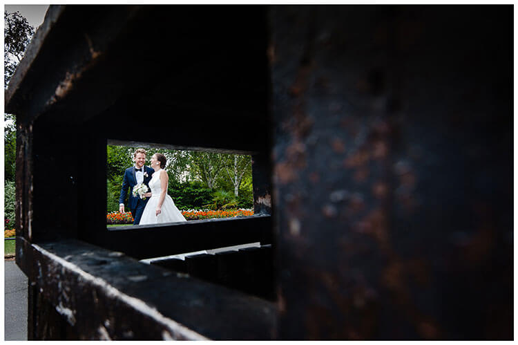 Laughing bride groom wlaking through Regents park in London, viewed through metal bin opening, after their wedding at Old marylebone town Hall wedding ceremony