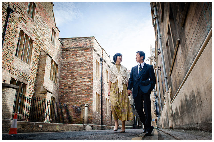 Couple hold hands and look at each other as they walk through the old streets of Cambridge during their pre wedding shoot favorite wedding photography 2018