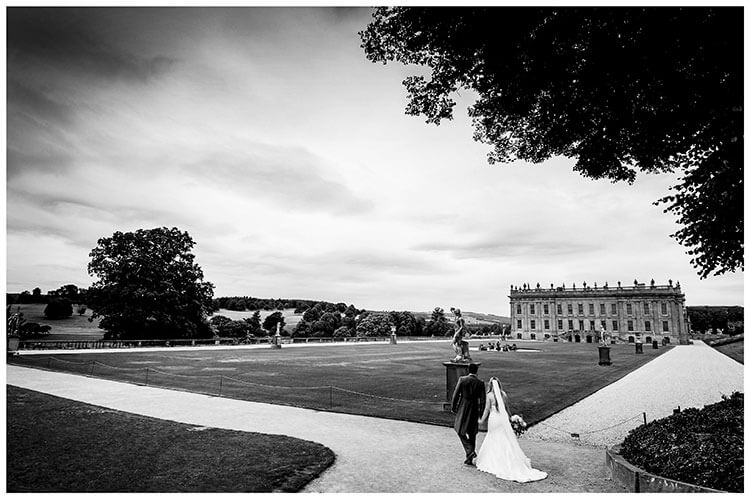 Couple hold hands as they walk towards Chatsworth House during their favourite wedding photography 2018