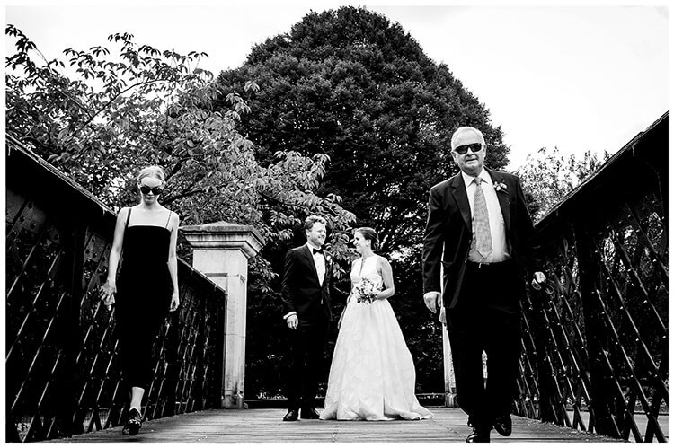 Couple standing on metal sided bridge in regents park london as two guests walk either side of them wearing sunglasses favourite wedding photography 2018