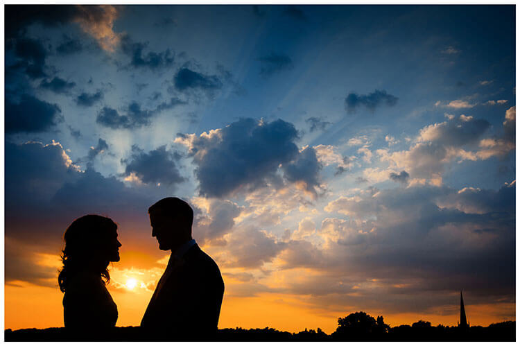 silhouette of wedding couple against a deep bllue and orange sky with church spire in background favourite wedding photography 2018