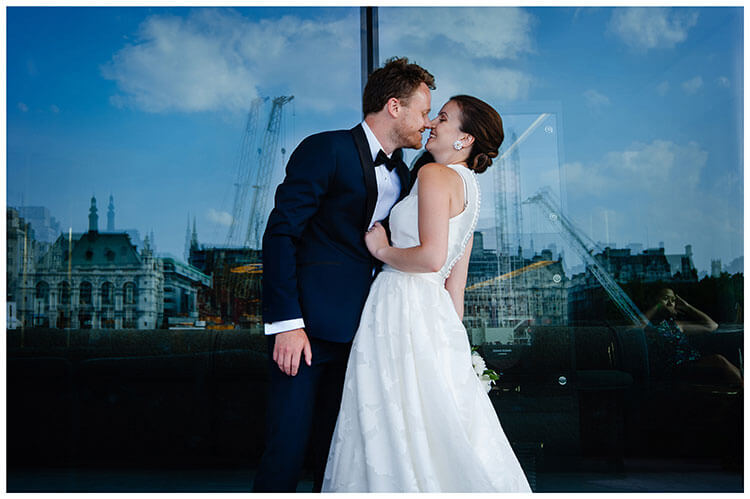 Groom goes to kiss bride in front of large window with london sky line reflected in window favourite wedding photography 2018