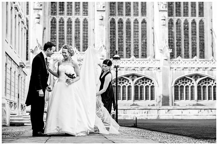 Bride touches grooms shoulder as they laugh Bridesmaid adjusts brides veil and dress Kings College Cambridge in Background