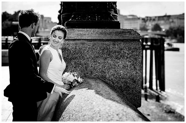 Bride smiles at groom as he touches her back standing on the Embankment in London favourite wedding photography 2018