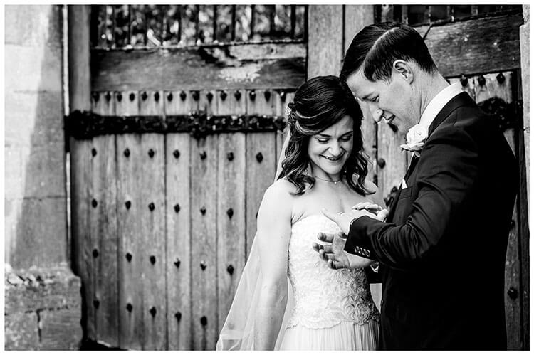 Groom shows bride his wedding band, whilst standing near old wooden doors of castle, she smiles and touches his hand