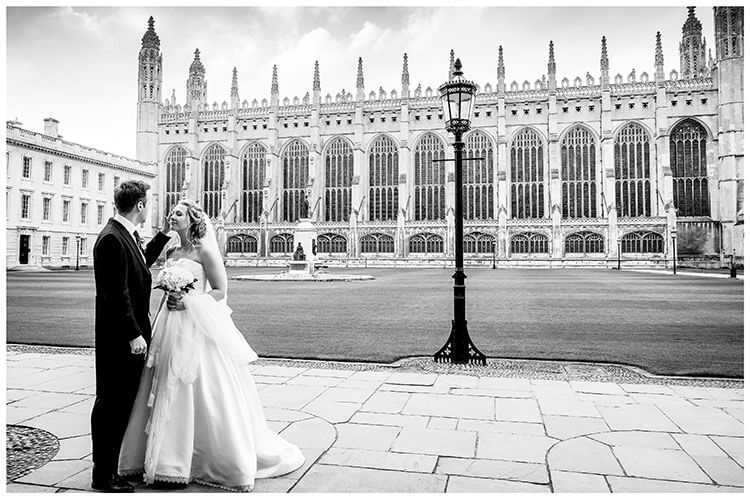 Groom brushes hair away from brides face with Kings College Chapel Cambridge in back ground favourite wedding photography 2018