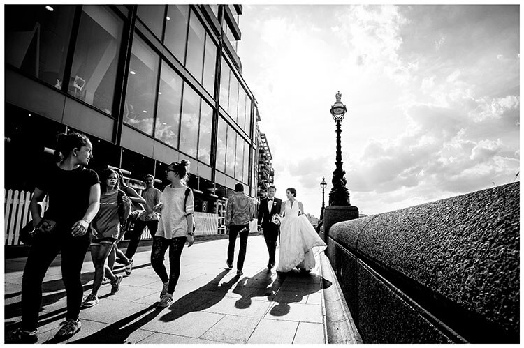 Bride lifts front of dress as she walks with groom along London Embankment yound girl in front of them turns back to look favourite weddiing photography 2018