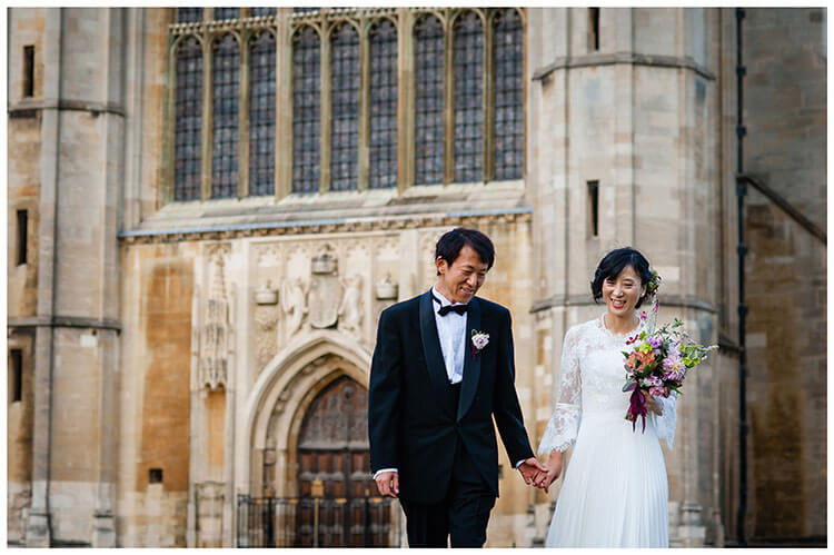 Smiling Asian bride and groom hold hands with Kings College Chapel in Background Favourite wedding photography 2018