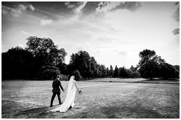 Bride and groom walking hand in hand through the grounds of Kings College Cambridge favourite wedding photography 2018