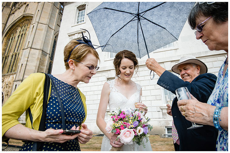 Bride show bouquet to guests as gentleman in hat holds umbrella over her head to protect her from the sun favouritew wedding photography 2018