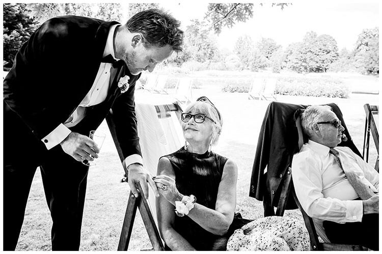 Mother sitting in a deck chair looks lovingly at her son the groom whilst checking his wedding band in Regents PArk