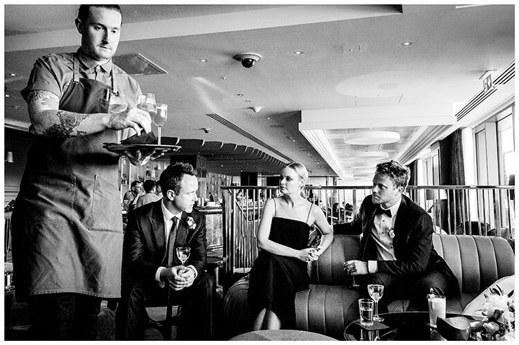 wedding guests Enjoying a cocktail with the groom as a waiter serves drinks at Sea Containers Bar in London favourite wedding photography 2018