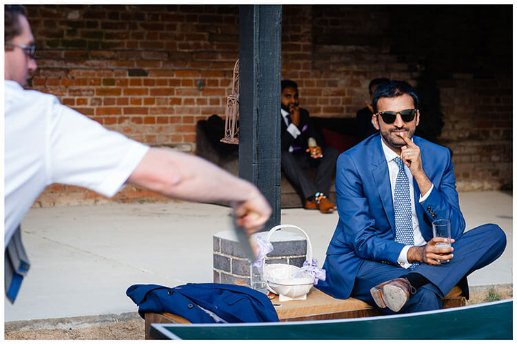 Guy in sunglasses sitting watching a game of table tennis at a wedding reception at Childerley hall Cambridgeshire Favourite wedding photography 2018