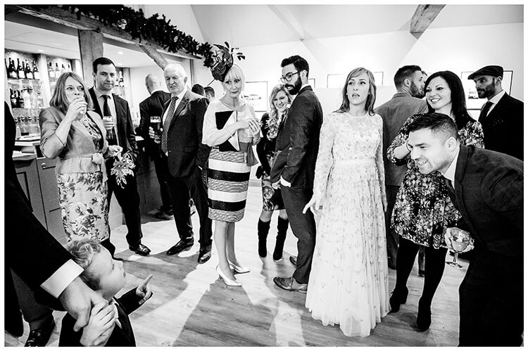 Wedding guests with Bride in bar at South farm looking at young paige boy who is asking a question favourite weddign photography 2018