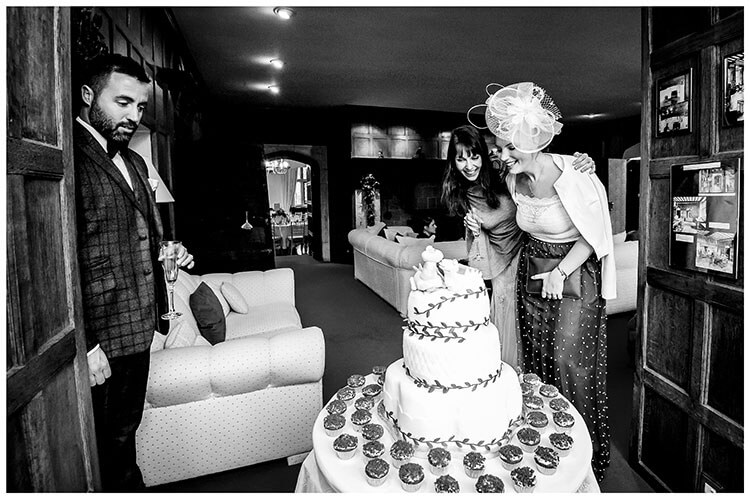3 guests looking at the wedding cake favourite wedding photography 2018