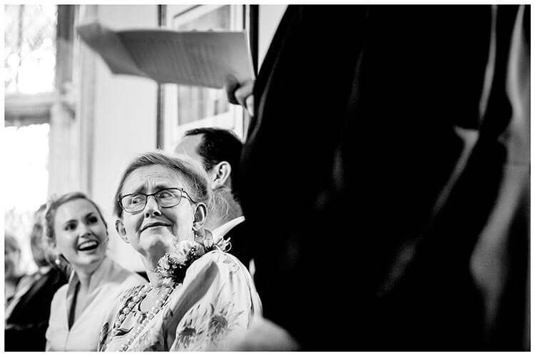 Look of suprise on mother of the brides face during speeches bride in background laughing favourite wedding photography 2108