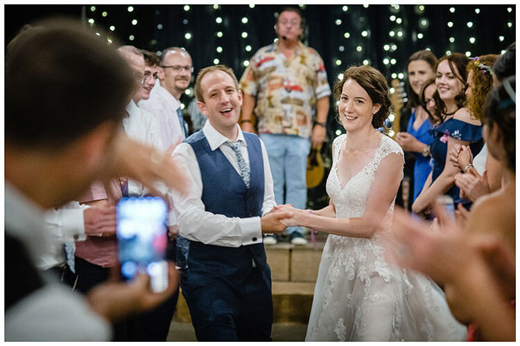 smiling bride and groom dance their way between two lines of guests during Cèilidh dance, guest takes photo on phone favourite wedding photography 2018