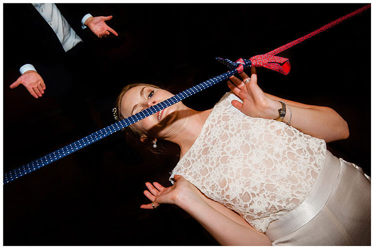 Bride limbo dancing under blue and red ties at Smallfield Place favourite wedding photography 2018