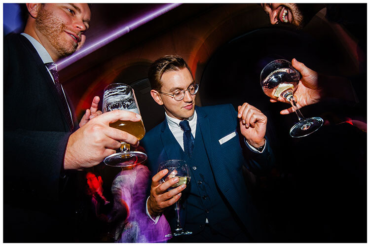 Thrre guys on the dance floor holding glasses of drink Favourite wedding photography Chatsworth House 2018