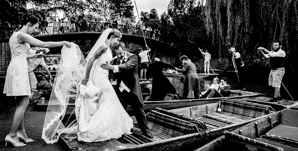 Bridesmaid holds Brides Veil as she is helped by her Groom on to a punt watched by passers by on a bridge in the background during a Queens College Cambridge wedding