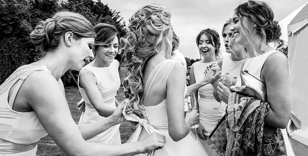 Bride surrounded by bridesmaids laughing and tying up her dress ribbon during rection for a cambridge village wedding