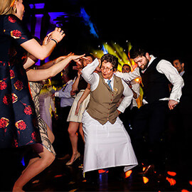 Your Investment - Groom dancing with mature waitress on dance floor cheered on by guests