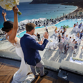 Destination Wedding - Bride Groom wave at guests from balcony at Hotel in Mykonos