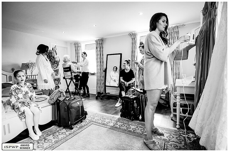 award winning wedding photography - bride getting ready as bridesmaid steams wedding dresses and flower girls watches while sat on bed
