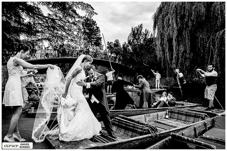 bride helped by groom and bridesmaid onto punt watched by crowds on bridge