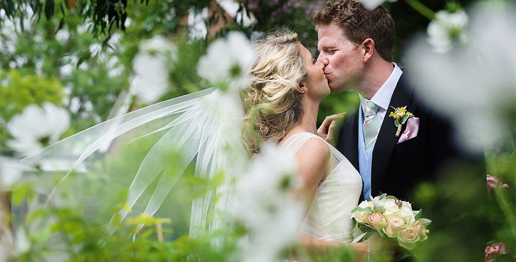 Brides veil billows in the wind as she kisses her groom in the flowered garden