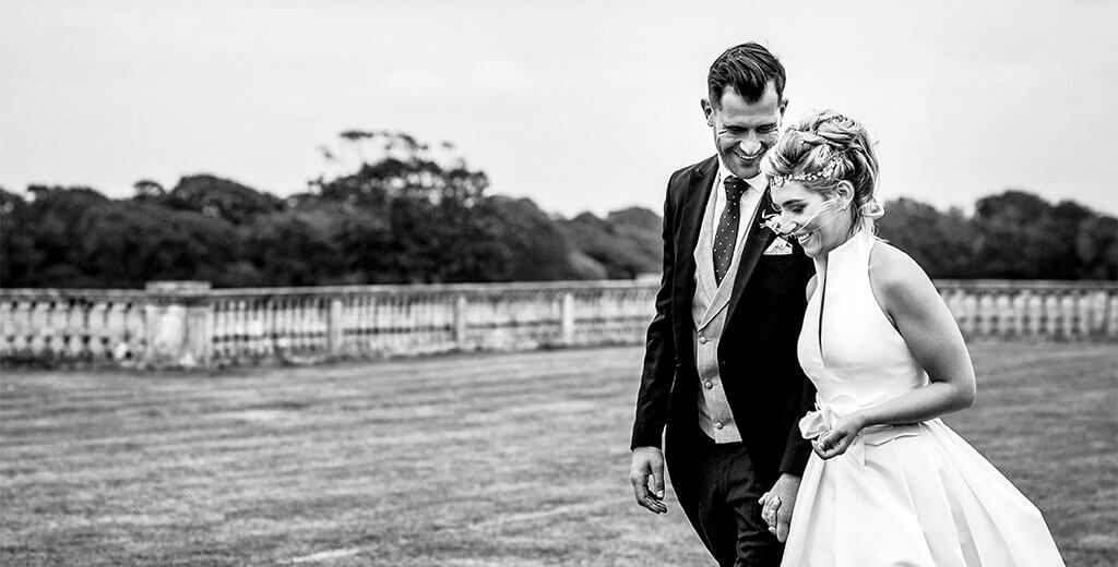 Smiling groom turns to his bride while they walk through the grounds of Pylewell park in hampshire
