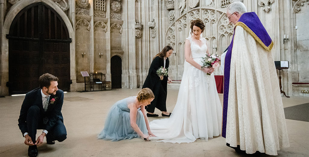 bride and vicar looking down at bridesmaid as she cleans brides dress in entrance of Kings College Chapel, usher ties shoe lace, prior to walking down aisle