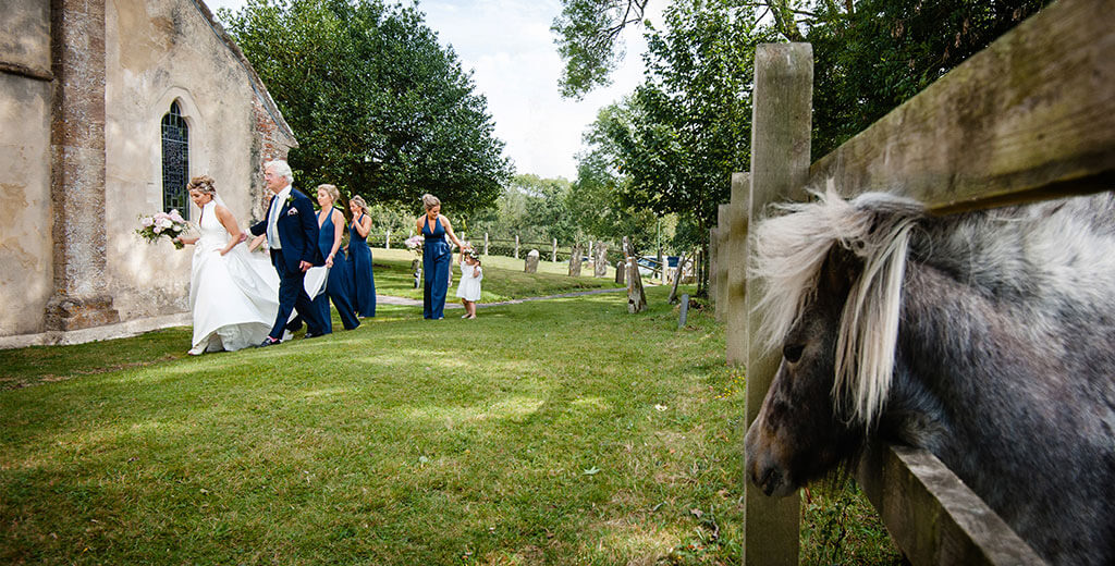small pony with head through fence watches as Bride walks towards St John the baptist Church in the hampshire Village of Boldre accompanied by father bridesmaids and flower girl