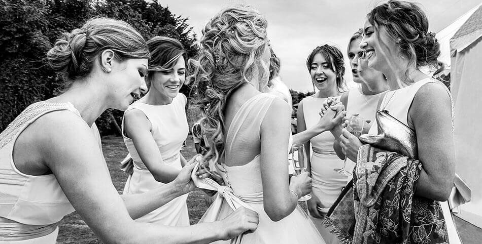 Bride surrounded by bridesmaids laughing and tying up her dress ribbon during reception for a Cambridge village wedding