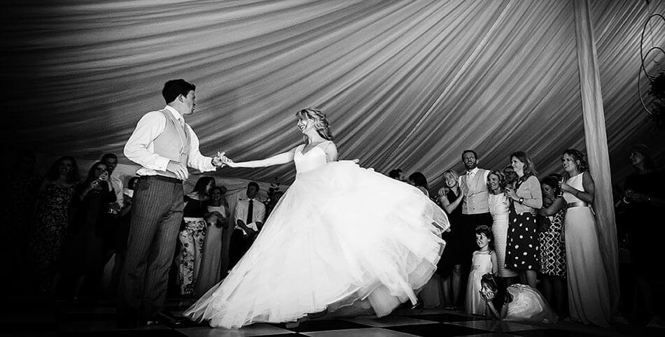 Cambridge Wedding Photographer Marquee wedding first dance bride swishes amazing dress as guests and flower girls watch