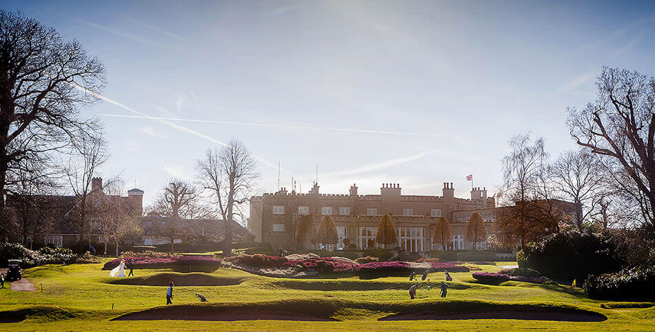 Wentworth Golf Club Surrey Bride groom walking across golf course club house in background by Creative Cambridge Wedding Photographer