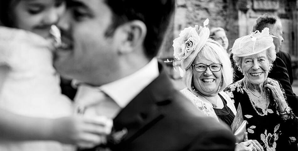 Elderly ladies smile at groom as he embraces flowergirl during Cambridgeshire wedding